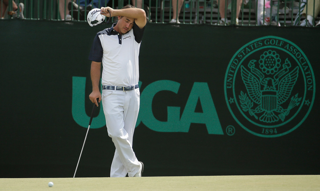. Brooks Koepka wipes his face on the the 11th green during the first round of the U.S. Open golf tournament in Pinehurst, N.C., Thursday, June 12, 2014. (AP Photo/Charlie Riedel)