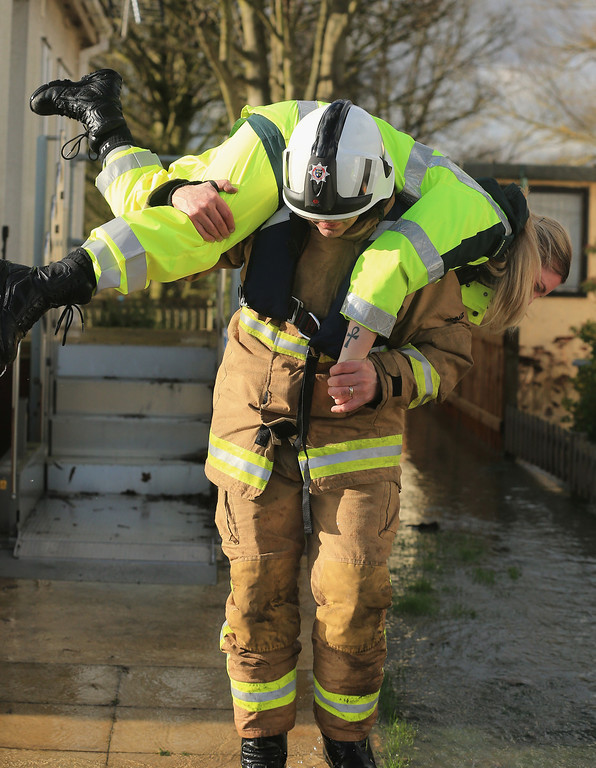 . A firefighter carries a paramedic through floodwater on February 11, 2014 in Chertsey, United Kingdom. The Environment Agency contiues to issue severe flood warnings for a number of areas on the river Thames in the commuter belt west of London. With heavier rains forecast for the coming week people are preparing for for the water levels to rise.  (Photo by Christopher Furlong/Getty Images)