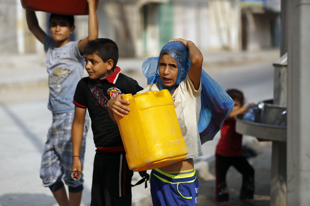 . A Palestinian boy holds a plastic container near a public tap on August 26, 2014 in Gaza City. Most residents in the Palestinian enclave suffered from water shortages even before the recent fighting between Hamas militants and Israel but now Monzer Shoblak, an official from the local water board, said war damage meant that Gaza was pumping 50 percent less water.  MOHAMMED ABED/AFP/Getty Images