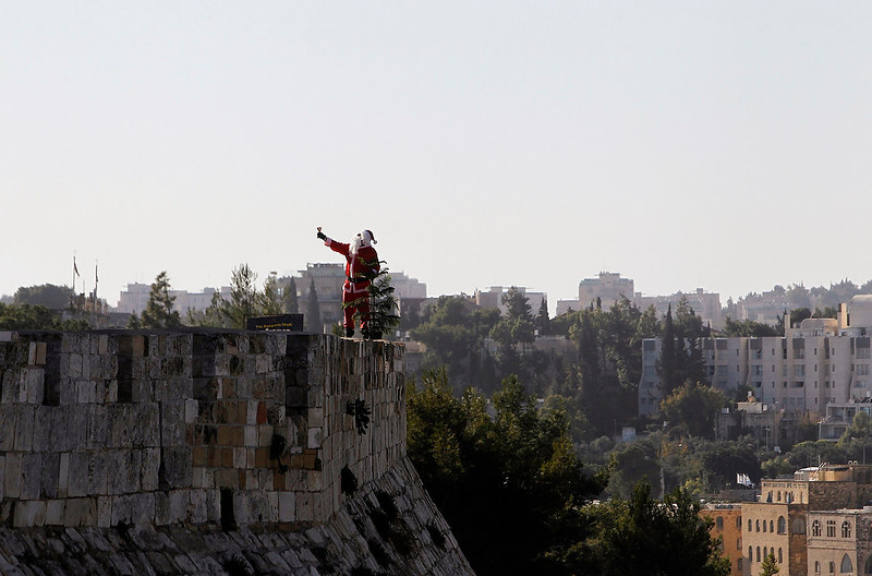 . Israeli-Arab Issa Kassissieh, dressed in a santa claus costume, rings a bell in front of the walls surrounding Jerusalem\'s Old City during a Christmas tree distribution by Jerusalem\'s municipality on December 23, 2012.   REUTERS/Ronen Zvulun