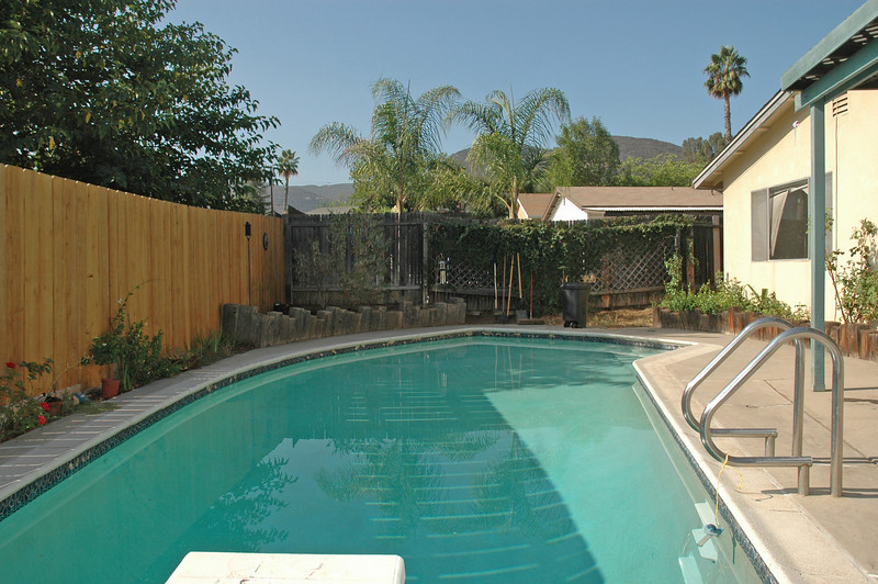 Backyard in-ground pool with covered patio to the right.