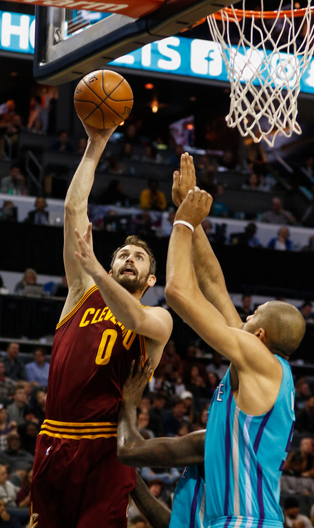 . Cleveland Cavaliers forward Kevin Love, left, shoots over Charlotte Hornets guard Nicolas Batum in the second half of an NBA basketball game in Charlotte, N.C., Saturday, Dec. 31, 2016. Cleveland won 121-109. (AP Photo/Nell Redmond)