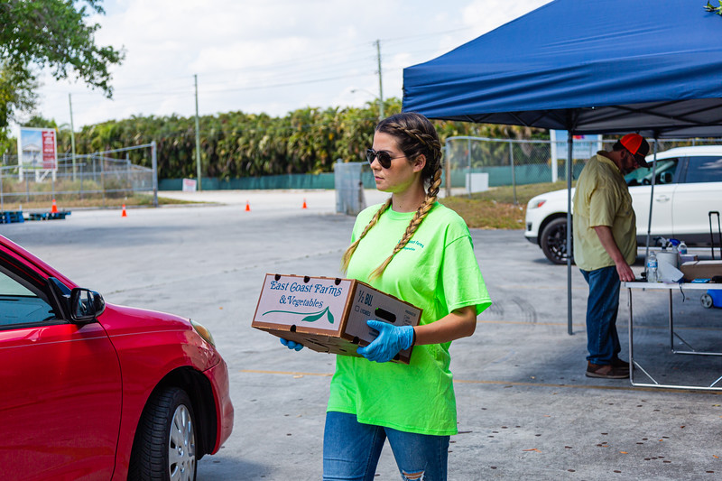 Katelyn Garcia, Director of New Business for East Coast Farms & Vegetables in Lake Worth, carries a box of vegetables to a customer's car on Thursday, March 26, 2020. East Coast Farms is usually a wholesaler of farm-fresh fruits and vegetables, but for the past week, they have operated as a curbside pickup for the community. They offer $10 boxes of farm-fresh produce and a la carte items, such as melons and pineapples. [JOSEPH FORZANO/palmbeachpost.com]