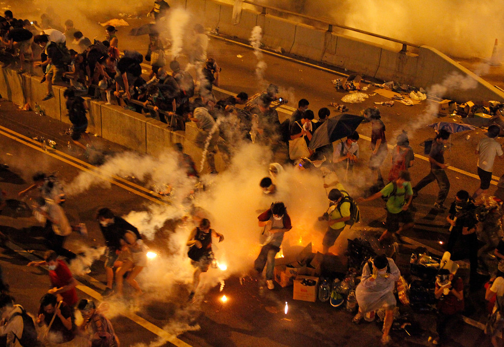. Riot police use tear gas against protesters after thousands of people blocked a main road at the financial central district in Hong Kong, Sunday, Sept. 28, 2014. Hong Kong police used tear gas on Sunday and warned of further measures as they tried to clear thousands of pro-democracy protesters gathered outside government headquarters in a challenge to Beijing over its decision to restrict democratic reforms for the city. (AP Photo)