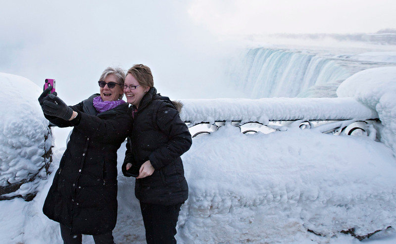 . Visitors Rosalie Vissers, left, and Rachel Houter take a photo near masses of ice formed around the Canadian \'Horseshoe\' Falls in Niagara Falls, Ontario, Canada, Thursday, Feb. 19, 2015. (AP Photo/The Canadian Press,Aaron Lynett)