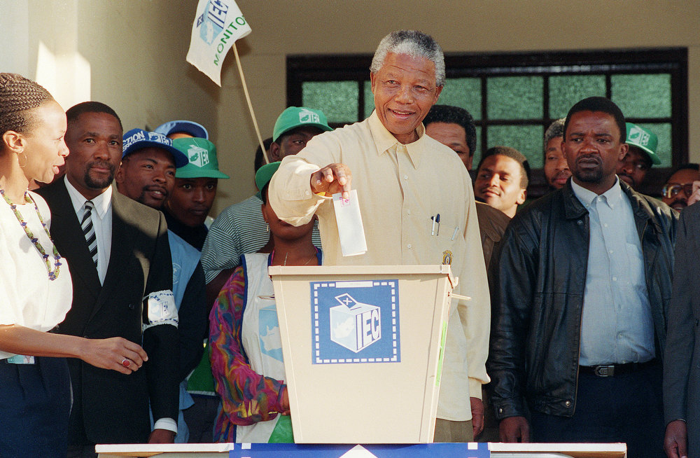 Description of . African National Congress (ANC) President Nelson Mandela smiles broadly 27 April 1994 in Oshlange, black township near Durban, as he casts his historic vote during South Africa's first democratic and all-race general elections. (Photo credit should read WALTER DHLADHLA/AFP/Getty Images)