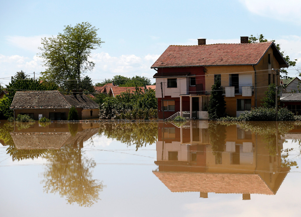 . Houses reflected in a flooded street in Obrenovac, some 30 kilometers (18 miles) southwest of Belgrade, Serbia, Monday, May 19, 2014. Belgrade braced for a river surge Monday that threatened to inundate Serbia\'s main power plant and cause major power cuts in the crisis-stricken country as the Balkans struggle with the consequences of the worst flooding in southeastern Europe in more than a century.  (AP Photo/Darko Vojinovic)