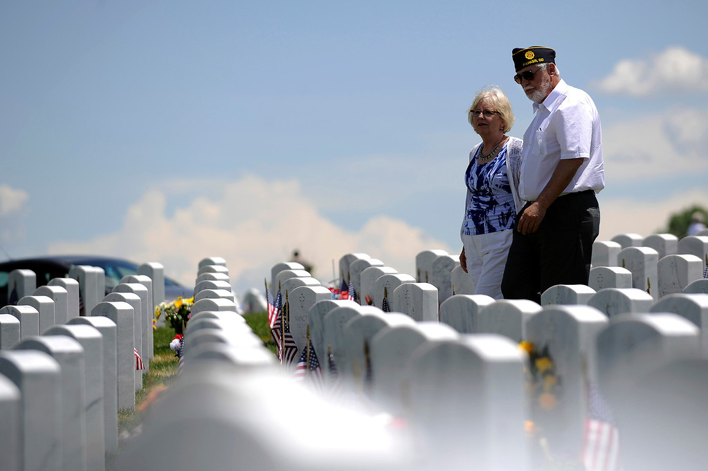 . Karl Goebel and Lucia McConnell walk amongst the headstones as they visit several graves during a Memorial Day ceremony at Fort Logan Cemetery in Denver, Colorado on May 26, 2014. (Photo by Seth McConnell/The Denver Post)