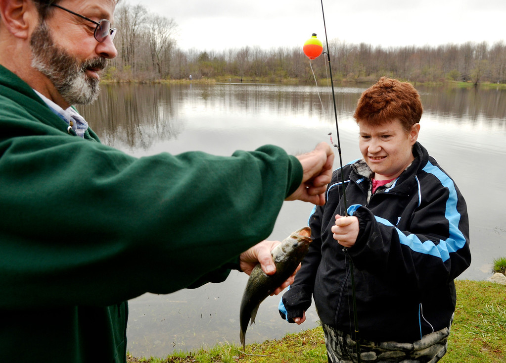 . Jeff Forman/JForman@News-Herald.com Volunteer Tom Hunter helps Carol Jamieson take her fish off the hook during the Lake Metroparks Fantastic Fishing program for people with disabilities April 30 at Hidden Lake in Leroy Township.