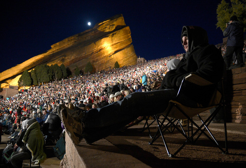 . Bobby Fuchs of Aurora, CO, who dressed for the cool predawn temperatures, enjoys the singing at the opening of the service. Thousands of people turned out for the sixty sixth annual Easter sunrise service at Red Rocks Amphitheatre in Golden on March 31st, 2013.The sun rose at 6:45 am under cloudless skies and this year\'s service was pleasant with warmer temperatures than in previous years.  The service, sponsored by the Colorado Council of Churches, was led by Reverend Dr. Jim Ryan and presided over by Reverend Dr. Janet Forbes.  (Photo By Helen H. Richardson/ The Denver Post)