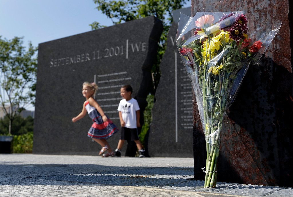 . Nevaeh Lewis, left, and Jonathan Wilson move through the September 11 Memorial in Indianapolis, Wednesday, Sept. 11, 2013 where a bouquet of flowers was placed to honor the victims of the 9/11 attacks on the 12th anniversary at the base of one of two beams taken from the World Trade Center. (AP Photo/Michael Conroy)