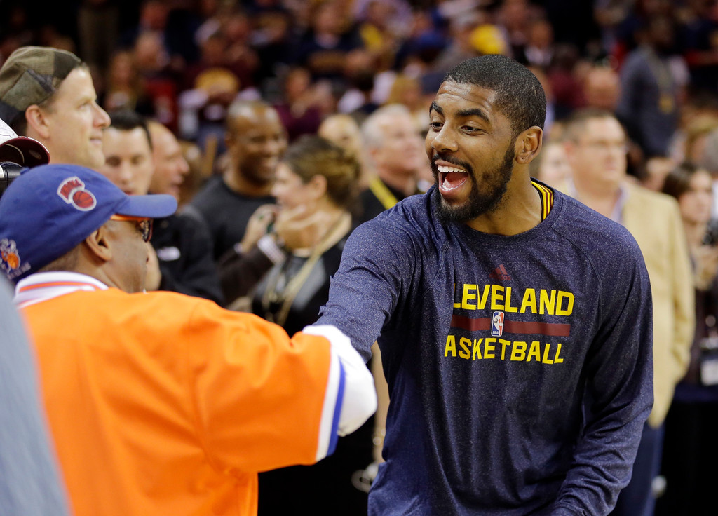. Cleveland Cavaliers\' Kyrie Irving, right, greets file maker Spike Lee before an NBA basketball game against the New York Knicks Thursday, Oct. 30, 2014, in Cleveland. (AP Photo/Tony Dejak)
