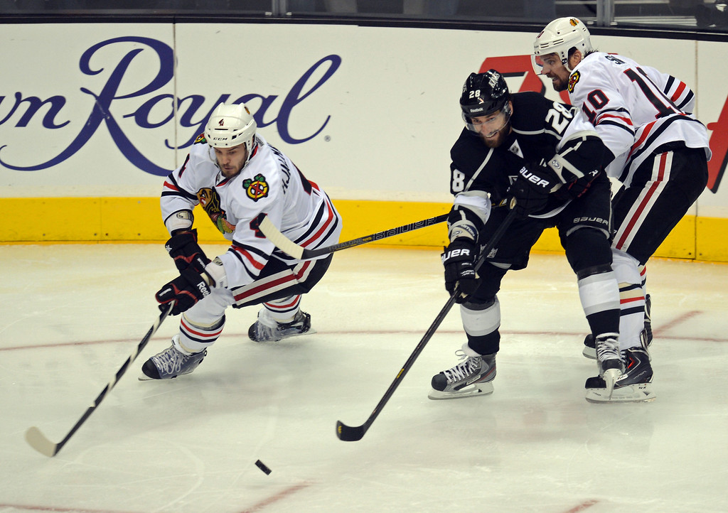 . The Kings\' Jarret Stoll #28 battles with Blackhawks\' Niklas Hjalmarsson #4 and Patrick Sharp #10 in the 1st period during game 4 of the Western Conference finals at the Staples Center in Los Angeles June 6, 2013. (David Crane/Los Angeles Daily News)