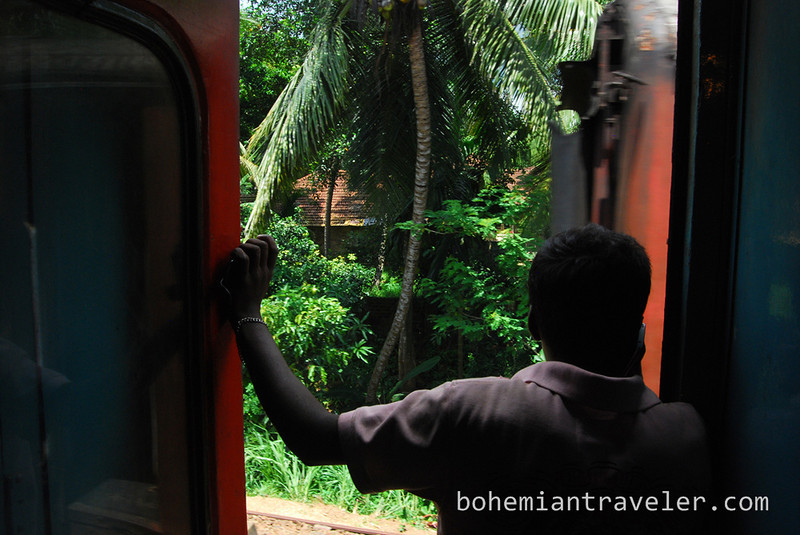 Man satands on Sri Lanka train door talking on mobile.jpg