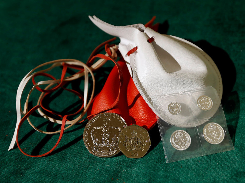 . Examples of the two purses on display showing the coins that Britain\'s Queen Elizabeth II distributed during the Maundy service, at Christ Church Cathedral on March 28, 2013 in Oxford, England. The Maundy money was today distributed by the Queen to 87 women and 87 men, who each received two purses, one red and one white. A 5 GBP coin and 50 pence coin commemorating the 60th anniversary of The Queen�s Coronation in the red purse. The white purse contains the uniquely minted Maundy Money. This takes the form of silver one, two, three and four penny pieces, the sum of which equals the number of years the Monarch\'s age. (Photo by Kirsty Wigglesworth - WPA Pool/Getty Images)