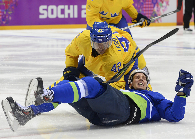 . Sweden\'s Jimmie Ericsson (top) vies with Slovenia\'s Robert Sabolic during the Men\'s Ice Hockey Quarterfinals Sweden vs Slovenia at the Bolshoy Ice Dome during the Sochi Winter Olympics on February 19, 2014. (JONATHAN NACKSTRAND/AFP/Getty Images)