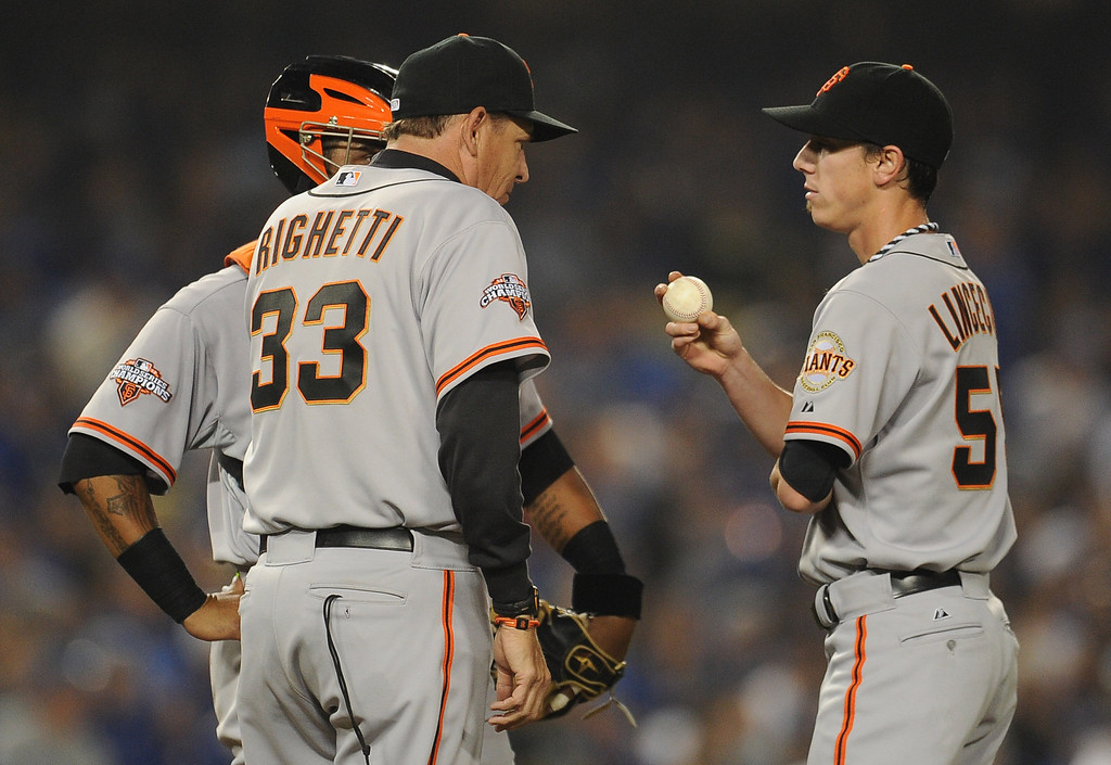 . San Francisco Giants pitching coach Dave Righetti (33) talks with starting pitcher Tim Lincecum (55) after walking Los Angeles Dodgers\' Josh Beckett (not pictured) in the second inning of their baseball game against Los Angeles Dodgers on Wednesday, April 3, 2013 in Los Angeles. 