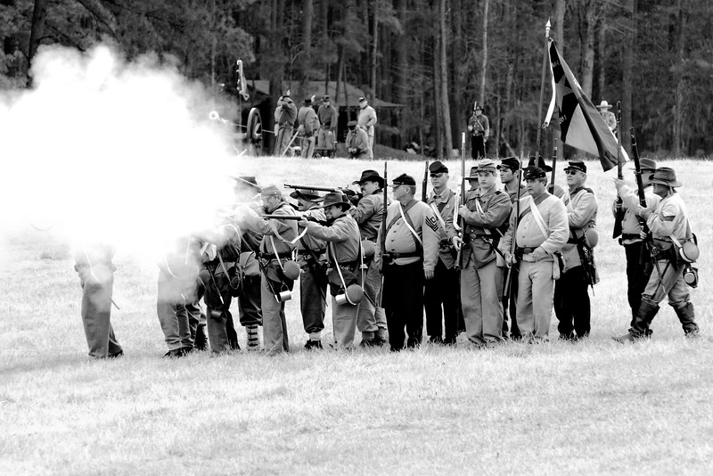 Confederate reenactors line up in two lines and return fire on the battlefield. The Skirmish at Gamble's Hotel happened on March 5, 1885 when 500 federal soldiers, under the command of Reuben Williams of the 12th Indiana Infantry, marched into Florence to destroy the railroad depot but were met by Confederate soldiers backed up with 400 militia. The reenactment, held by the 23rd South Carolina Infantry, was held at the Rankin Plantation in Florence, South Carolina on Saturday, March 5, 2011. Photo Copyright 2011 Jason Barnette