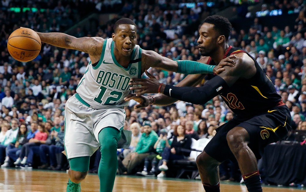 . Boston Celtics\' Terry Rozier (12) drives past Cleveland Cavaliers\' Jeff Green (32) during the first quarter of an NBA basketball game in Boston, Sunday, Feb. 11, 2018. (AP Photo/Michael Dwyer)