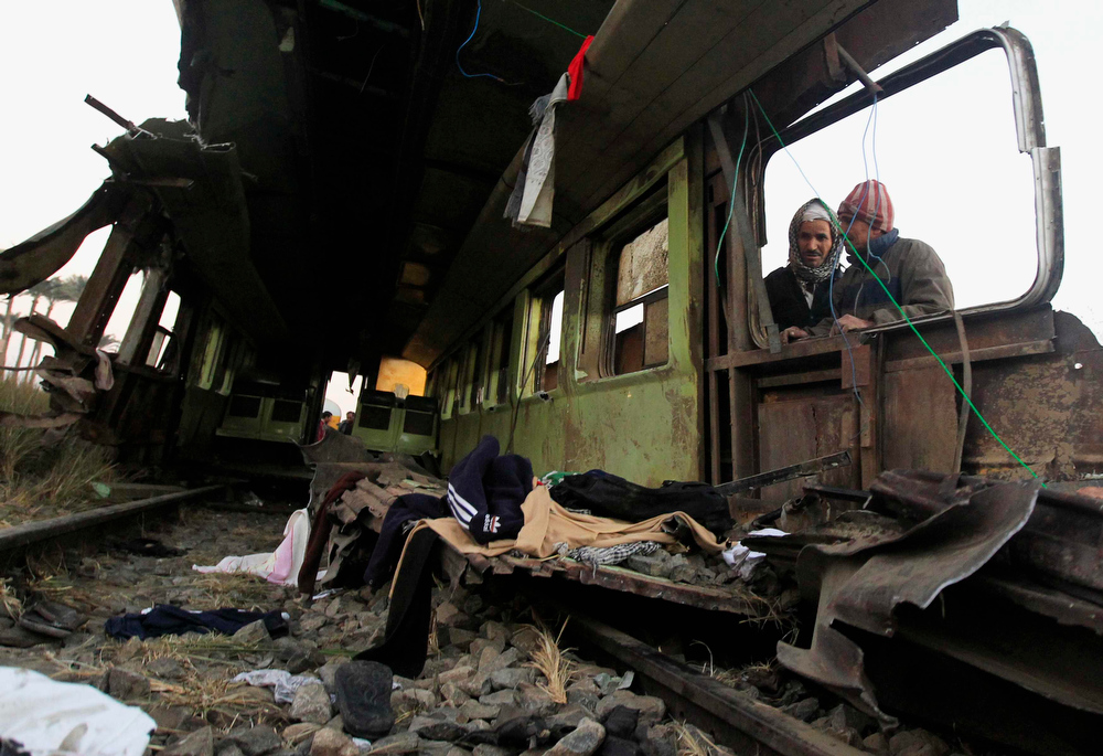 . Men inspect the wreckage of a military train crash in the Giza neighbourhood of Badrashin, about 40 km (25 miles) west of Cairo, January 15, 2013. A military train carrying young recruits to an army camp derailed in a Cairo suburb on Tuesday, killing 19 people and injuring 107, Egypt\'s health ministry spokesman said.   REUTERS/Mohamed Abd El Ghany