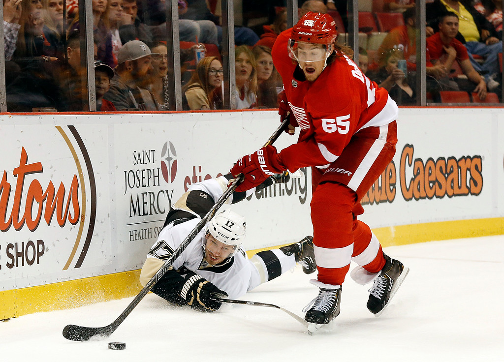 . Detroit Red Wings defenseman Danny DeKeyser (65) takes the puck from Pittsburgh Penguins\' Blake Comeau (17) in the first period of a NHL preseason hockey game in Detroit Wednesday, Oct. 1, 2014. (AP Photo/Paul Sancya)