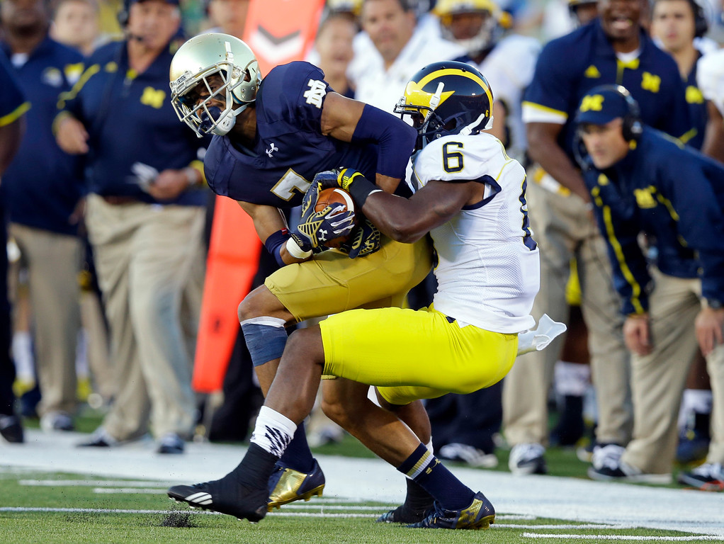 . Notre Dame wide receiver William Fuller, left, is tackled by Michigan defensive back Raymon Taylor after a catch during the first half of an NCAA college football game in South Bend, Ind., Saturday, Sept. 6, 2014. (AP Photo/Michael Conroy)