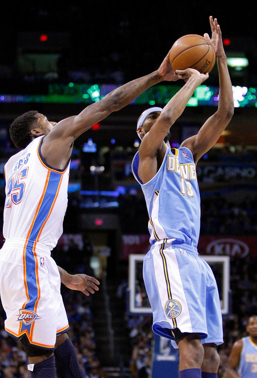 . Oklahoma City Thunder guard DeAndre Liggins, left, forces the ball out of the hands of Denver Nuggets forward Corey Brewer, right, during the first quarter of an NBA basketball game in Oklahoma City, Wednesday, Jan. 16, 2013.  (AP Photo/Alonzo Adams)