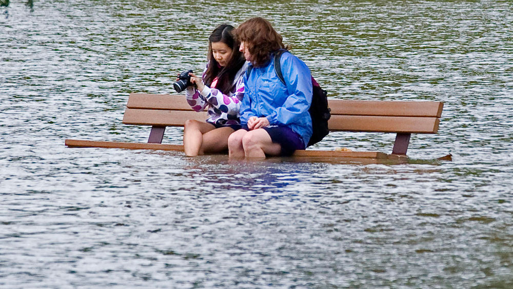 Description of . Claire Paulsen, 17, and her mother Gretchen Paulsen look at pictures they took of floodwaters from the Winooski River on Volunteers Green in Richmond, Vt. on Friday Oct. 1, 2010. (AP Photo/The Burlington Free Press, Glenn Russell)