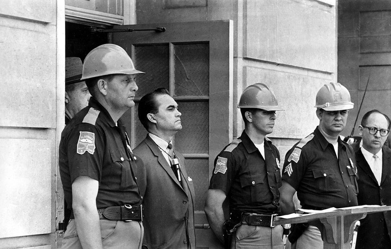 . Gov. George Wallace blocks the entrance to the University of Alabama as he turned back a federal officer attempting to enroll two black students at the university campus in Tuscaloosa, Ala., June 11, 1963.  The 43-year-old governor stands with highway patrolmen who are on duty to prevent violence.  (AP Photo)