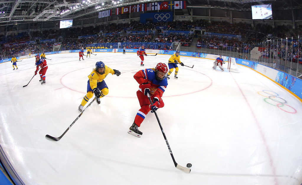 . Angelina Goncharenko #2 of Russia handles the puck against Jenni Asserholt #4 of Sweden in the first period during the Women\'s Ice Hockey Preliminary Round Group B game on day six of the Sochi 2014 Winter Olympics at Shayba Arena on February 13, 2014 in Sochi, Russia.  (Photo by Martin Rose/Getty Images)