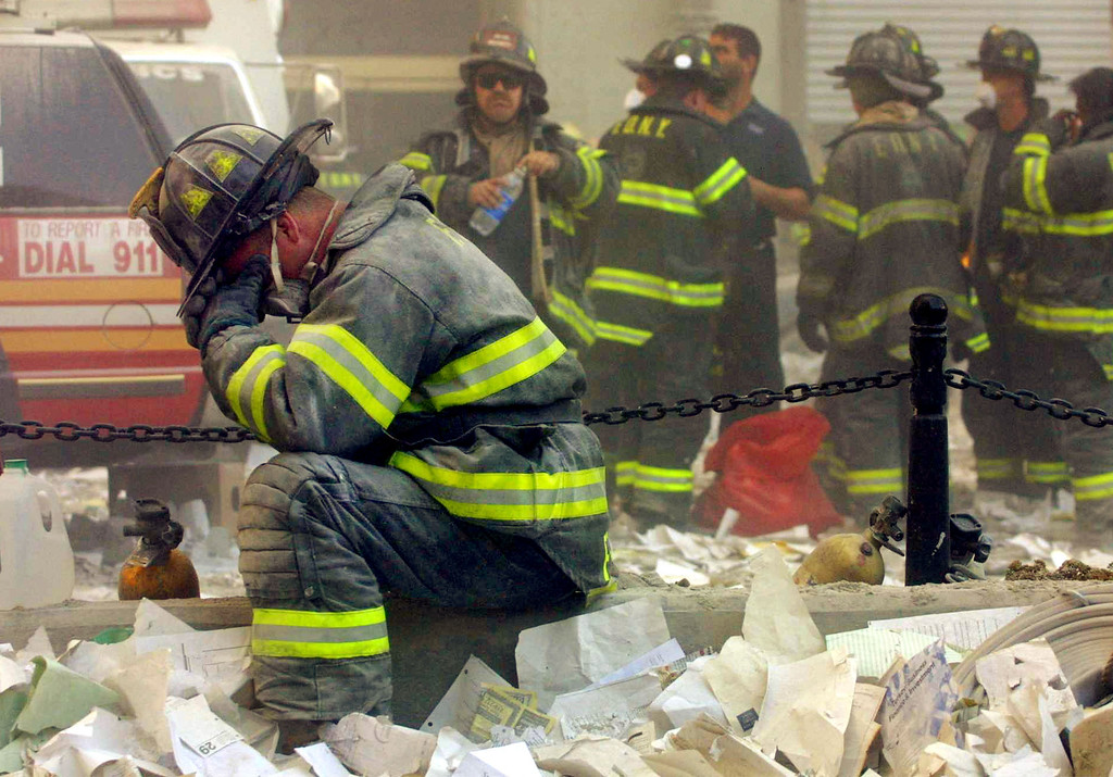 . A firefighter breaks down after the World Trade Center buildings collapsed September 11, 2001 after two hijacked airplanes slammed into the twin towers in a terrorist attack. (Photo by Mario Tama/Getty Images)
