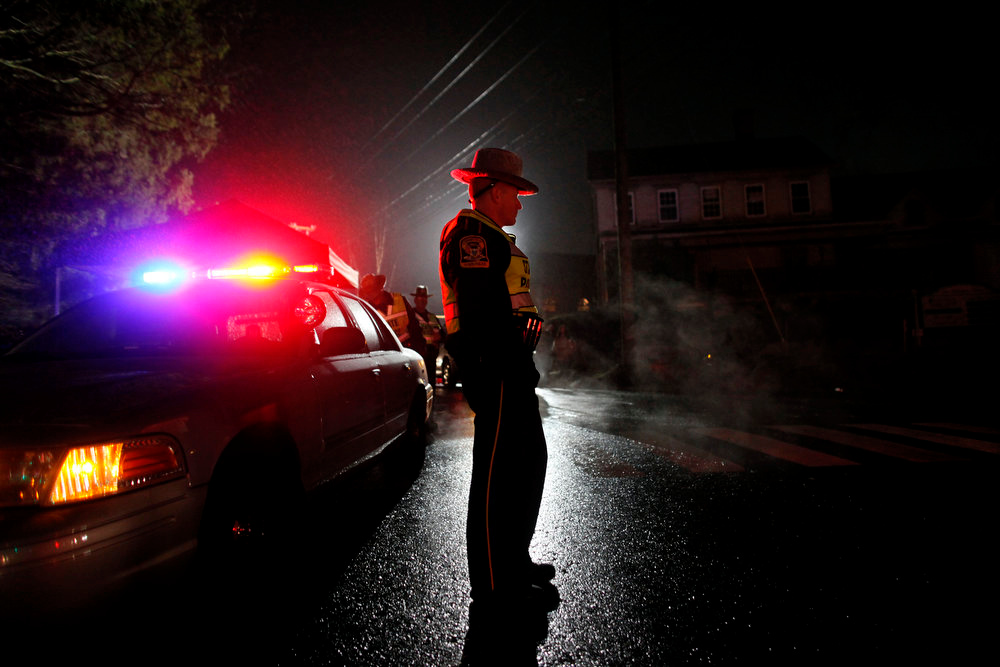 Description of . A Connecticut state trooper mans a checkpoint on the road leading towards Sandy Hook Elementary School, Monday, Dec. 17, 2012, in Newtown, Conn. A gunman walked into Sandy Hook Elementary School in Newtown Friday and opened fire, killing 26 people, including 20 children. (AP Photo/Jason DeCrow)