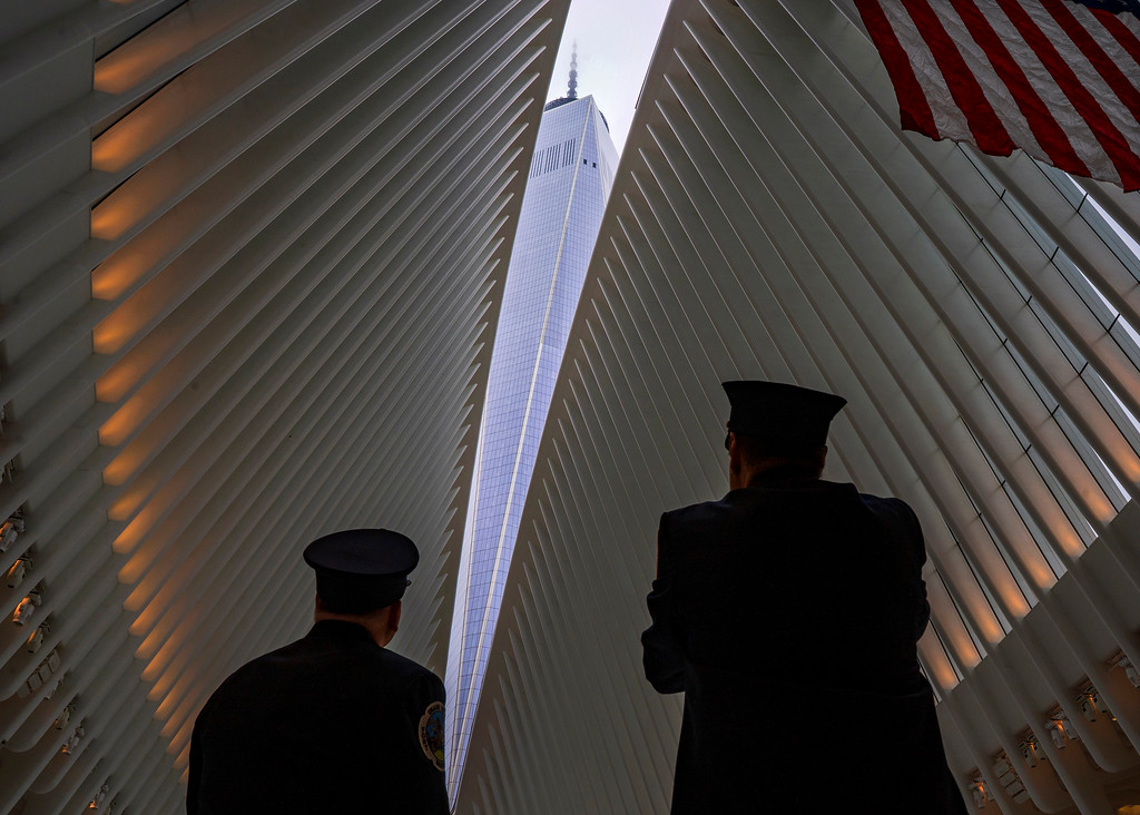. Two members of the New York City fire department look towards One World Trade Center through the open ceiling of the Oculus, part of the World Trade Center transportation hub in New York, Tuesday, Sept. 11, 2018, the anniversary of 9/11 terrorist attacks. The transit hall ceiling window was opened just before 10:28 a.m., marking the moment that the North Tower of the World Trade Center collapsed on September 11, 2001. (AP Photo/Craig Ruttle)