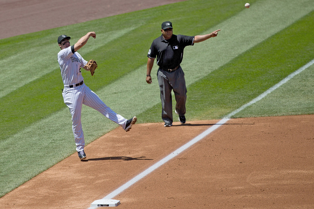 . Third baseman Nolan Arenado #28 of the Colorado Rockies makes an off-balance throw to first base for the second out of the second inning as third base umpire Adrian Johnson signals the ball is in fair territory during a game against the Arizona Diamondbacks at Coors Field on May 22, 2013 in Denver, Colorado. (Photo by Justin Edmonds/Getty Images)