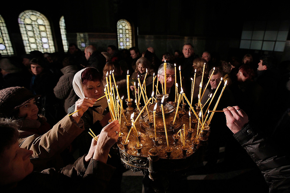 . People light candles during a Christmas Eve mass in Alexander Nevski Cathedral in Sofia, December 25, 2012. Bulgaria, unlike some other Orthodox countries, celebrates Christmas on December 25.   REUTERS/Dobrin Kashavelov