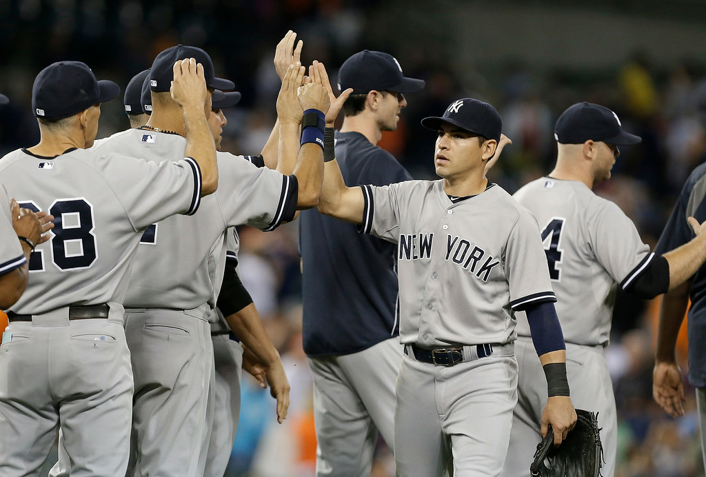 . New York Yankees\' Jacoby Ellsbury congratulates teammates after they defeated the Detroit Tigers 8-4 in a baseball game in Detroit, Wednesday, Aug. 27, 2014. (AP Photo/Paul Sancya)