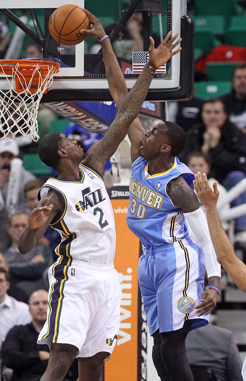 . Denver Nuggets\' Quincy Miller (30) scores on Utah Jazz\'s Marvin Williams (2) in the first quarter during an NBA basketball game Monday, Jan. 13, 2014, in Salt Lake City. (AP Photo/Rick Bowmer)