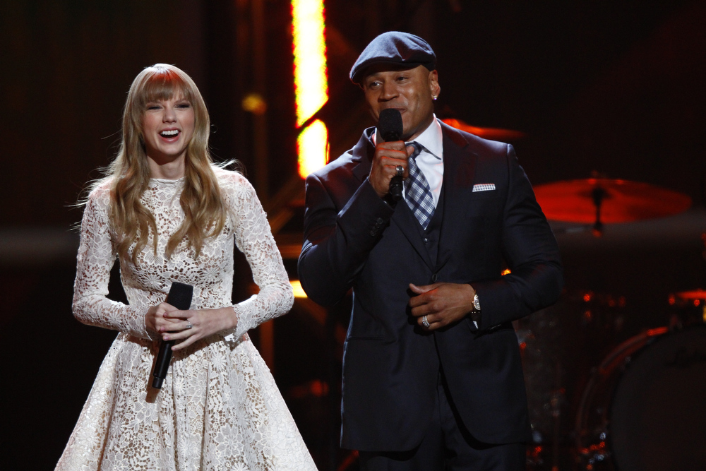 Description of . Hosts Taylor Swift, left, and LL Cool J speak onstage at the Grammy Nominations Concert Live! at Bridgestone Arena on Wednesday, Dec. 5, 2012, in Nashville, Tenn. (Photo by Wade Payne/Invision/AP)