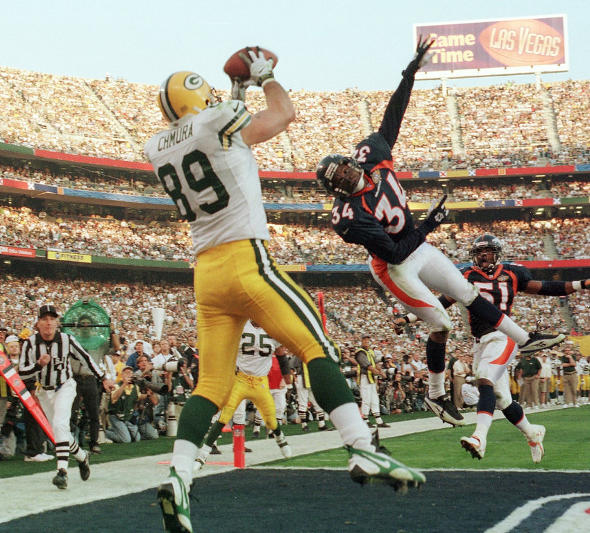 . Caption: Green Bay Packers Mark Chmura comes down with a second  quarter touchdown reception as Denver Broncos Tyrone Braxton covers on the play during Super Bowl XXXII.  (Andy Cross/The Denver Post)