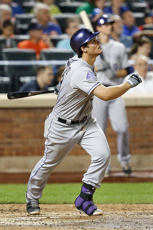 . Colorado Rockies\' Nolan Arenado hits an RBI sacrifice fly in the fifth inning of a baseball game against the New York Mets at Citi Field, Tuesday, Aug. 6, 2013, in New York. (AP Photo/John Minchillo)