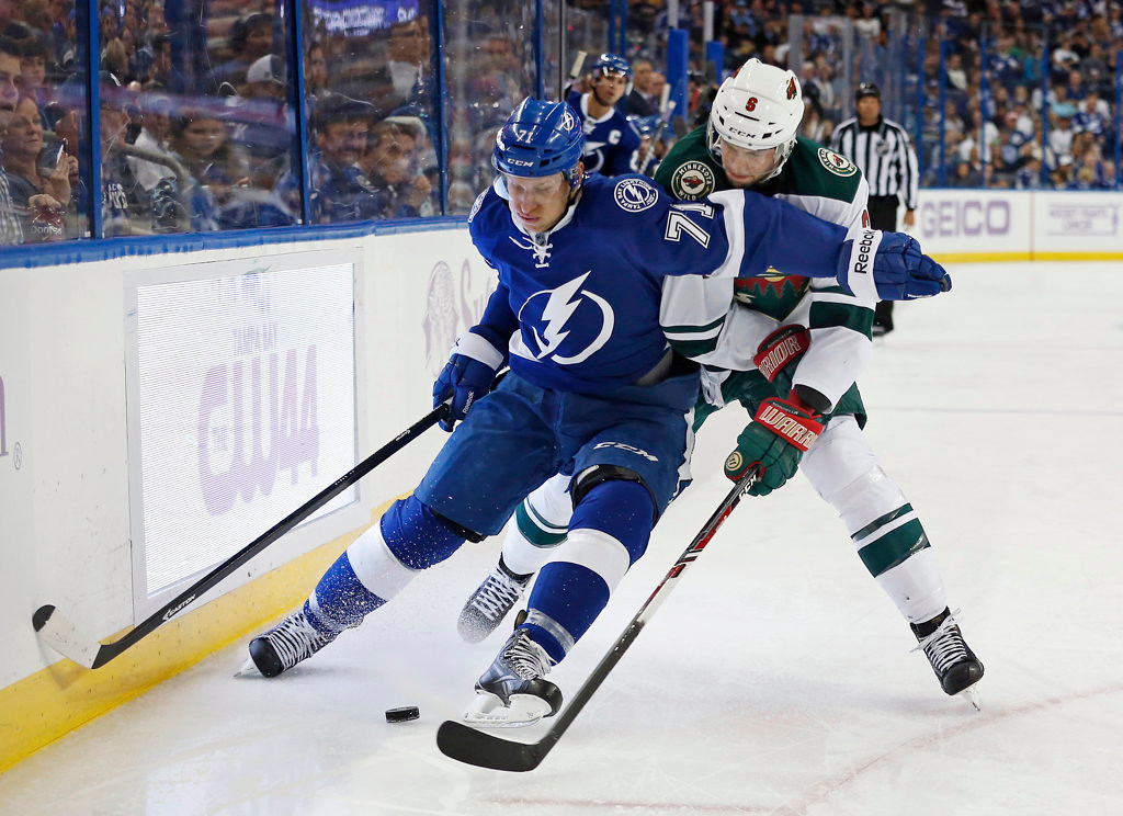 . Richard Panik #71 of the Tampa Bay Lightning fights off a check from Marco Scandella #6 of the Minnesota Wild. (Photo by Mike Carlson/Getty Images)