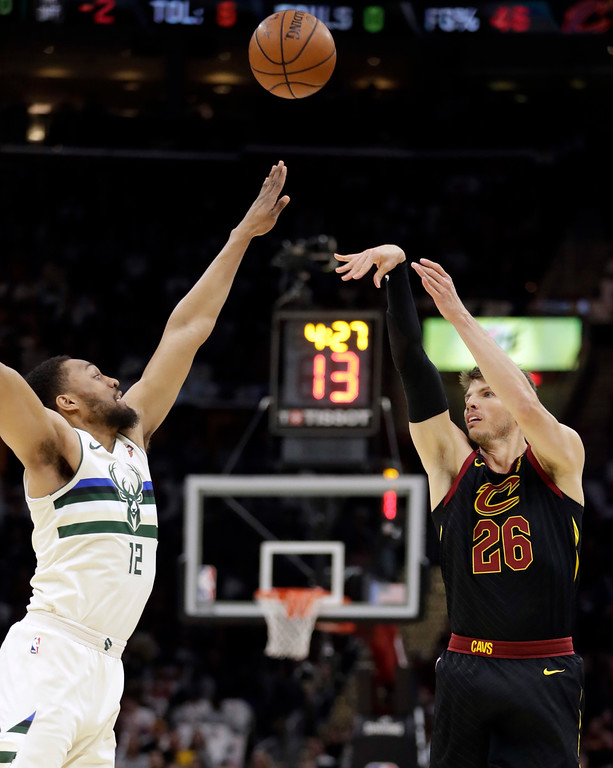 . Cleveland Cavaliers\' Kyle Korver (26) shoots over Milwaukee Bucks\' Jabari Parker (12) in the first half of an NBA basketball game, Monday, March 19, 2018, in Cleveland. (AP Photo/Tony Dejak)