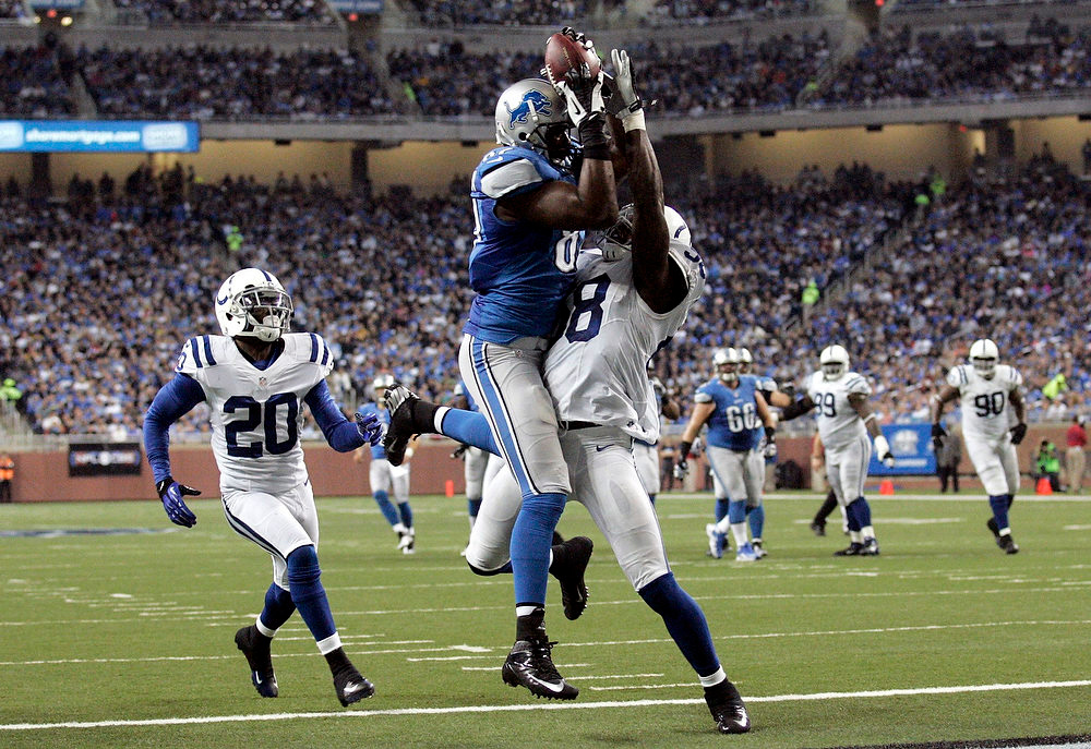 Description of . Detroit Lions tight end Brandon Pettigrew (C) completes a pass for a touch down past Indianapolis Colts Moise (R) Fokou during the first half of their NFL football game in Detroit, Michigan December 2, 2012.  REUTERS/Rebecca Cook