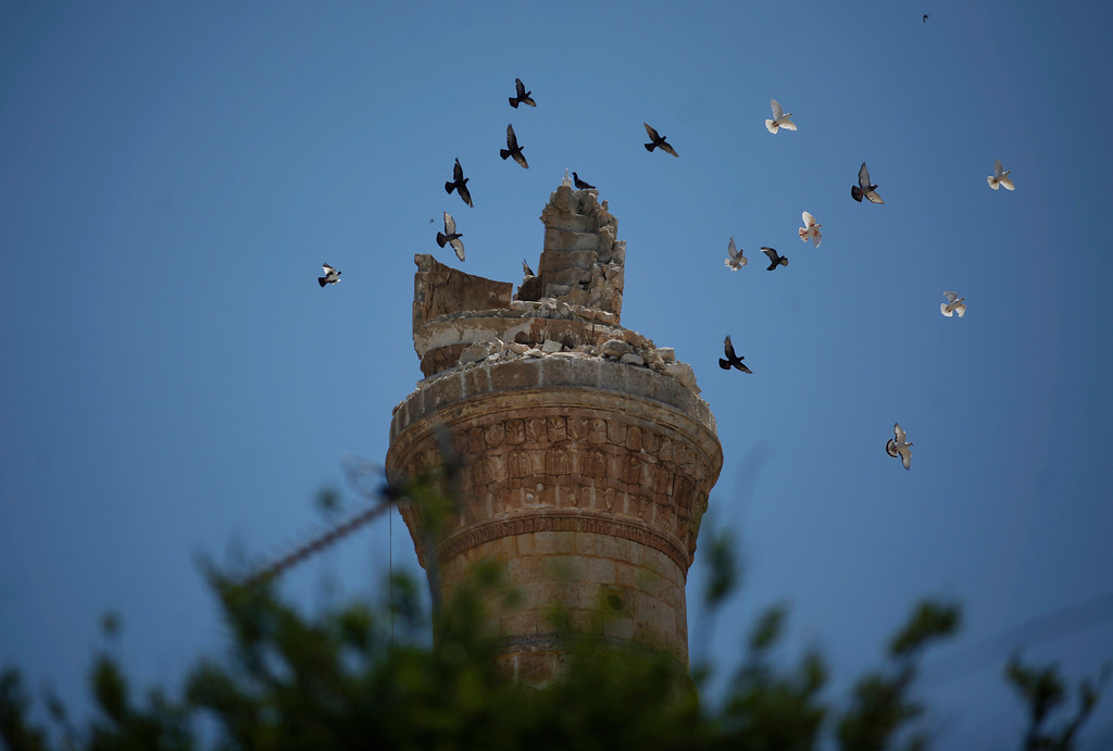 . FILE - Birds fly over the destroyed minaret of a mosque in the northern town of Ariha, on the outskirts of Idlib, Syria, Sunday, June 10, 2012. (AP Photo/Khalil Hamra, File)