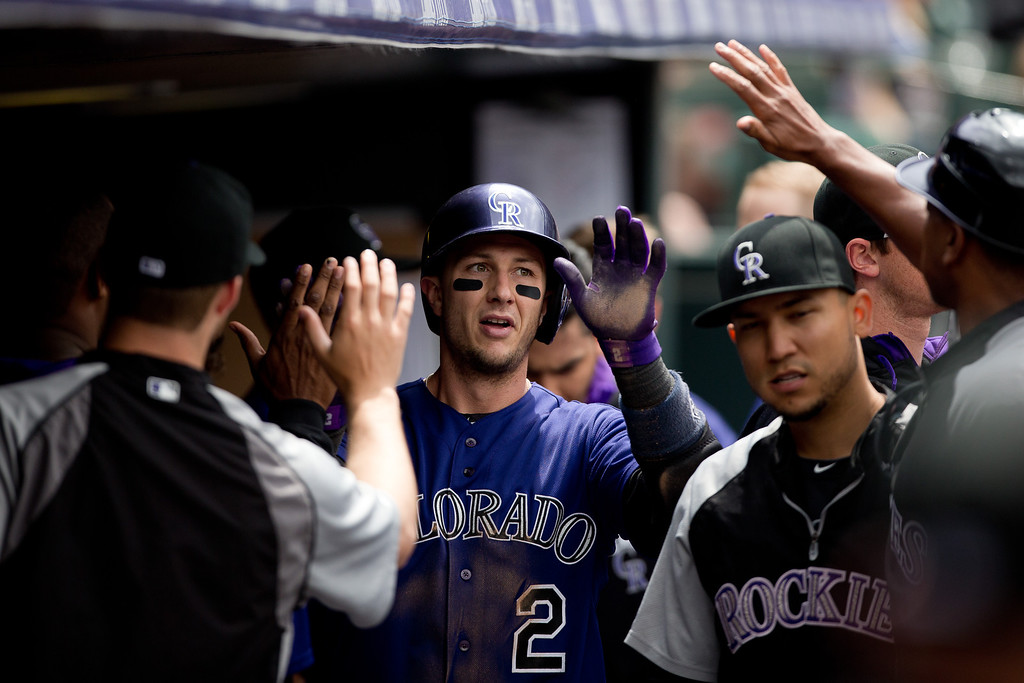 . DENVER, CO - JUNE 7:  Troy Tulowitzki #2 of the Colorado Rockies celebrates in the dugout after scoring during the second inning against the Los Angeles Dodgers at Coors Field on June 7, 2014 in Denver, Colorado. (Photo by Justin Edmonds/Getty Images)