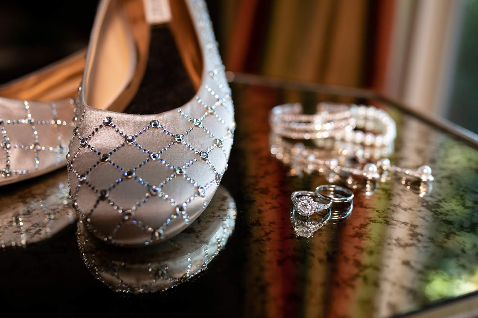 silver wedding shoes with pearl accents and bracelets sitting on a mirrored table