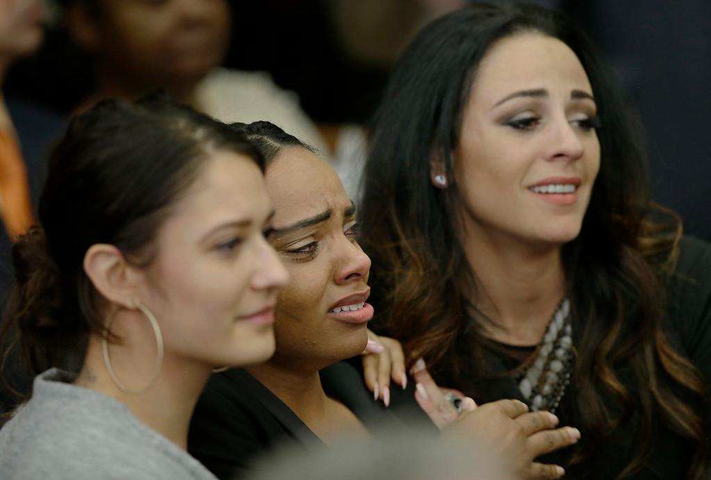 . Shayanna Jenkins Hernandez, center, the fiancee of former New England Patriots tight end Aaron Hernandez, is comforted as she reacts to Hernandez\'s double murder acquittal at Suffolk Superior Court Friday, April 14, 2017, in Boston. Hernandez stood trial for the July 2012 killings of Daniel de Abreu and Safiro Furtado who he encountered in a Boston nightclub. The former NFL player is already serving a life sentence in the 2013 killing of semi-professional football player Odin Lloyd. (AP Photo/Stephan Savoia, Pool)