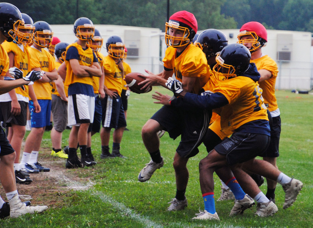 . Jon Behm - The Morning Journal<br> Olmsted Falls sophomore quarterback Kevin Eiseman is forced out of bounds by a pack of Bulldogs during Olmsted Falls\' first day of football practice on July 30.