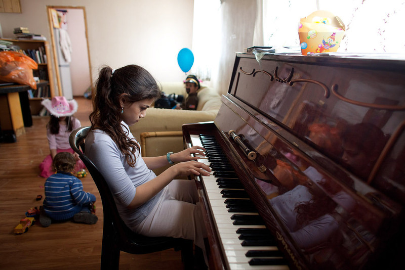 . A Jewish settler girl plays the piano as her brothers and sister wear costumes ahead of the Jewish festival of Purim February 22, 2013 at the settlement outpost of Havat Gilad, West Bank.  (Photo by Uriel Sinai/Getty Images)