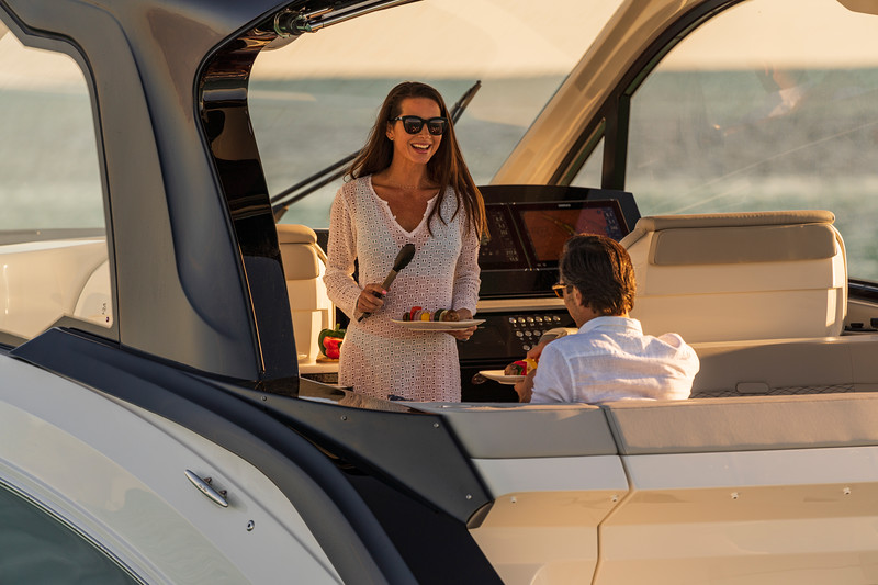 2021-Sundancer-370-Outboard-DAO370-lifestyle-couple-cooking-eating-cockpit-00318.jpg